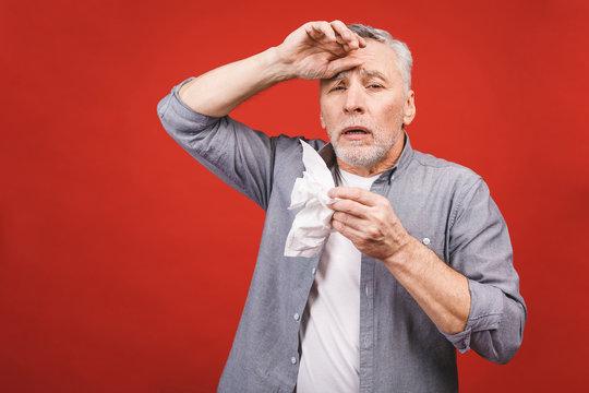 Sick senior man blowing his nose with tissue. having flu, aller