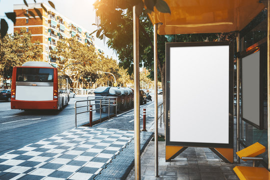 The bus stop with departing red bus and with blank poster mock-up inside; an advertising banner empty template inside of the stop of public transport; an empty placeholder for info billboard outdoors