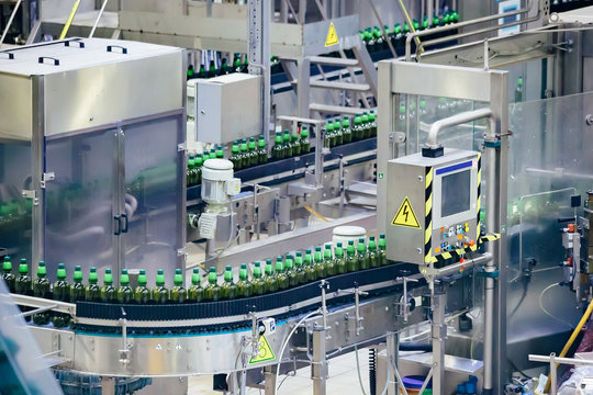 Automated beer bottling production line. Packed beer bottles on conveyor belt