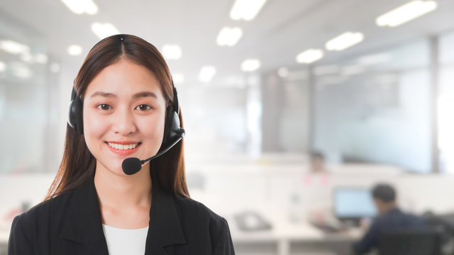 Portrait of Asian beautiful smiling woman customer support phone operator in office space banner background and copy space.Concept call center job service.