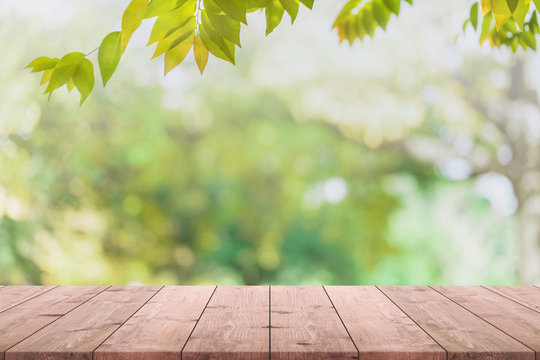 Empty wood table top and blurred view from green tree garden bokeh background - can used for display or montage your products.