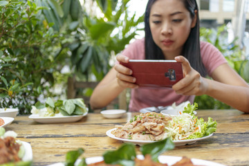 Woman is taking a photo of Thai food on the table.