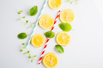 Colorful drinking paper straws and mint leaves, lemon slices on a white background