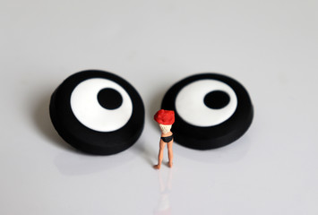A miniature woman changing clothes and miniature eyes.