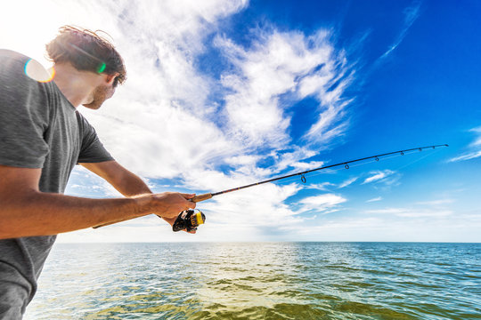 Man fishing in the sea from boat casting bait throwing line.