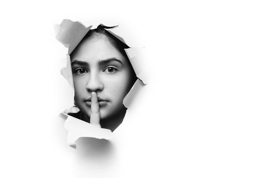 A teenage girl closes her lips with her index finger,making it clear to the viewer that you need to observe silence,keep a secret and not say too much. Сensorship and harassment of freedom of speech.