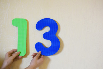 Hands holding number thirteen on yellow wall background with copy space for text. 13 anniversary birthday design or educational children toys for learning colors and numbers concept.