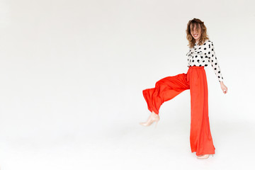 Stylish beautiful young hipster girl posing studio in wide red pants and polka dot shirt. Concept of stylish boho shooting. Advertising space