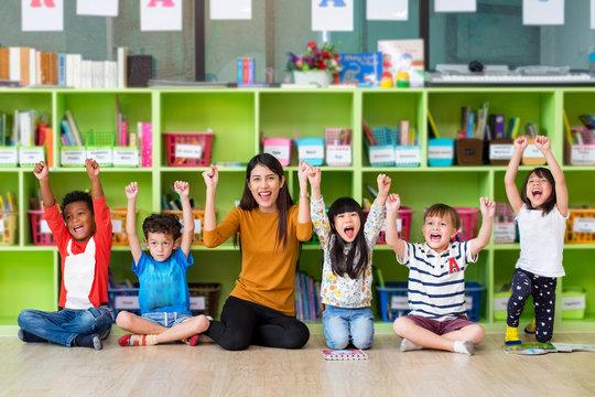 Happy Asian female teacher and mixed race kids in classroom,Kindergarten pre school concept.