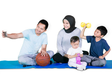 Attractive family taking selfie photo on mat