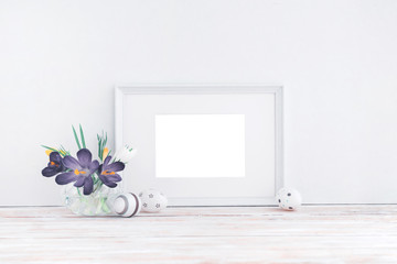 Empty white wooden frame, flowers and decorative eggs on white background with copy space. Mockup.