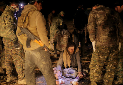 Fighters from the Syrian Democratic Forces (SDF) stand near an evacuated civilian, near the village of Baghouz, Deir Al Zor province