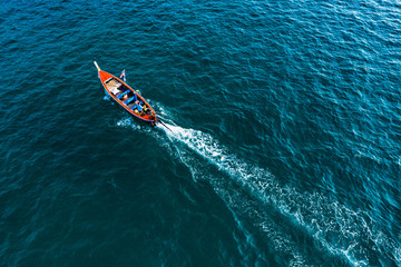 View from above, stunning aerial view of a beautiful long-tail boat with tourists on board sailing on a deep blue sea headed to Maya Bay, Phi Phi Island, Krabi Province, Thailand.