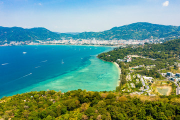 Wall Mural - View from above, stunning aerial view of Patong city skyline in the distance and the beautiful Tri Trang Beach bathed by a turquoise and clear sea in the foreground, Phuket, Thailand.
