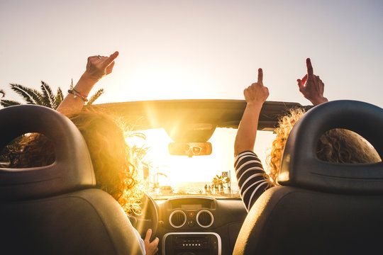 Couple of woman friends traveling and driving having a lot of fun dancing in the car with opened roof and summer vacation sunset ocean in front - concept of friendship together and nice lifestyle
