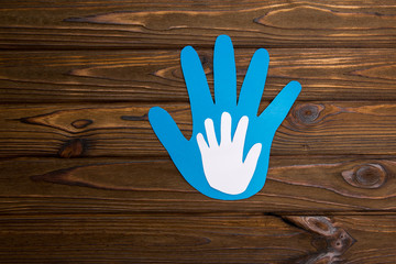 Silhouette of an adult and child's hand carved from a sheet of paper on a wooden background. family value.