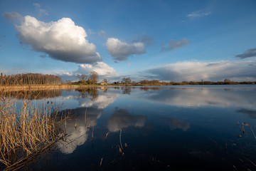 calm lake in bright sun light with reflections of clouds and trees and blue sky