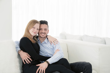 Couple is hugging, sitting on couch at home. True love. Beautiful young loving couple holding hands while sitting on the couch. Close-up