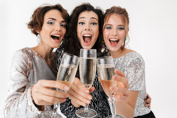 Young happy women friends posing isolated over white wall background. on a party.
