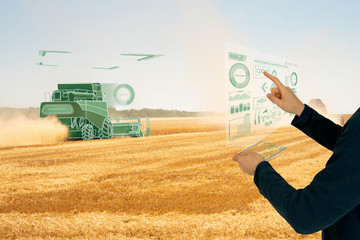 Wall Mural - Farmer controls autonomous harvester.