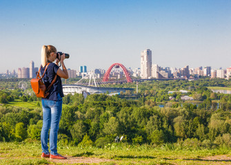 Woman traveler photographer make a photo of the city from the point of view
