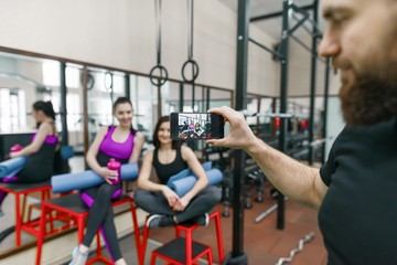 Young athletic smiling woman laughing in the gym, photographed on mobile phone. Fitness, sport, training, people, healthy lifestyle concept.