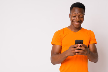 Portrait of young happy African man using phone