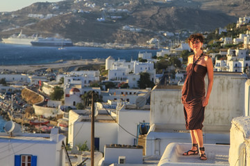 Girl in dress with Mykonos town, Greece