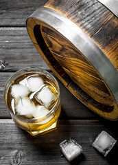 Whiskey in a glass with ice cubes and a barrel.