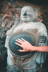 Hand touching the belly of a laughing buddha stone statue in Yonggungsa Buddhist temple in Busan, South Korea