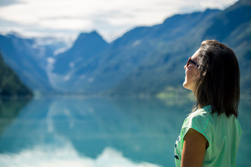 Portrait of young, beautiful woman standing near by mountain lake in Norway.