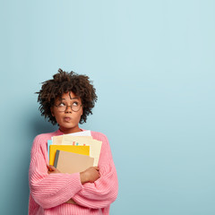 Photo of hesitant thoughtful Afro American student prepares for making home assignment, focused upwards, holds papers and textbooks, purses lips, wears transparent spectacles and oversized jumper