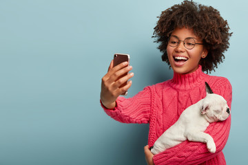 Beautiful cheerful dark skinned woman shoots online video about breed of dog for her blog, gives advice for followers how care this breed, takes picture of herself with pet via cellular, laughs