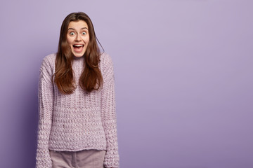 Emotional jovial dark haired woman being on heavens from pleasure, happy to recieve lump sum of money, has cheerful facial expression, wears knitted jumper isolated over purple studio wall, free space