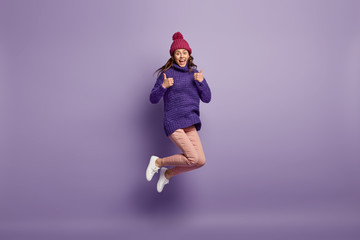 Full length size shot of carefree beaming woman jumps in air against purple background, has thumbs up, demonstrates okay sign, being sportive and active, full of energy, agrees with perfect thing