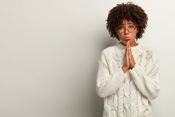 Photo of begging African American woman pleads with pitiful expression, holds hands in praying gesture, asks to give one more chance to improve, hopes for better, isolated on white studio wall