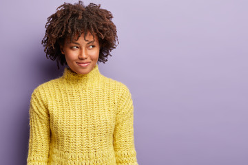 Headshot of curious satisfied dark skinned woman with curly haircut, looks away with intention or intriguing plan, wears yellow clothes, has something in mind, poses against purple wall, blank space
