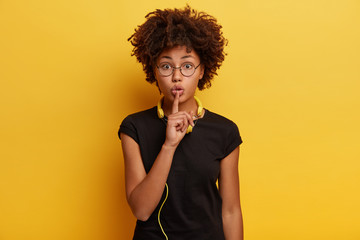 Shush, dont spread rumors. Secret black young woman makes hush gesture, enjoys audio track in modern yellow headphones, asks not tell which style of music she prefers. Leisure and hobby concept