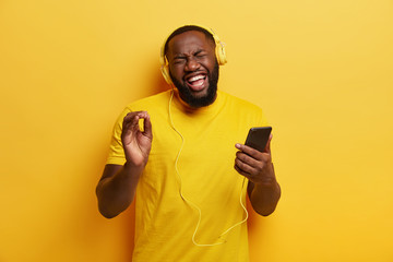 Hipster guy with dark skin, joyful expression, recalls nice memories while listens nice awesome song in headphones, sings loudly, expresses sincere emotions, wears apparel in one tone with background