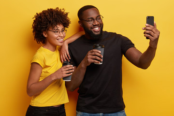Lovely dark skinned African couple take selfie with modern smart phone, drink coffee to go, smile broadly at camera, enjoy spare time, stands closely to each other against yellow background.