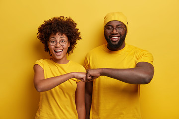 Studio shot of overjoyed satisfied woman and man with dark skin, give fist bump, agree to work together, have success in project work, wear yellow attire, pose in studio. Cooperation concept