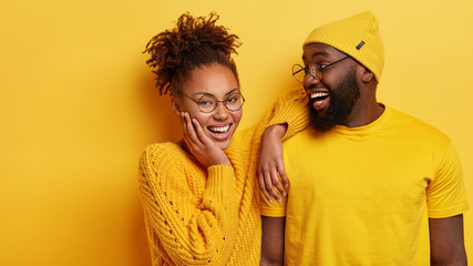 Happy Afro American couple in fashionable neat clothes, express joy, have pleasant friendly talk, cheerful expressions, enjoy togetherness, isolated over yellow background. Friendship and partnership
