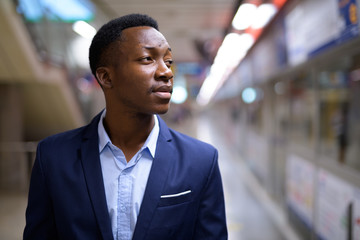 Young handsome African businessman waiting in the subway train station
