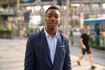 Young handsome African businessman in the city streets outdoors