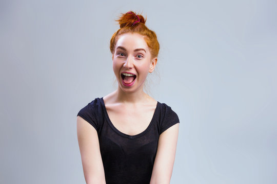 Amazed female model with red hair tied in knot, wearing black shirt , looking with bugged eyes and widely opened mouth on gray background