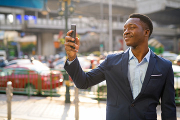 Young handsome African businessman taking selfie in the city streets outdoors
