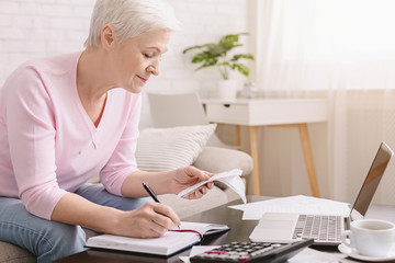 Senior woman bookkeeping bills and payments at home