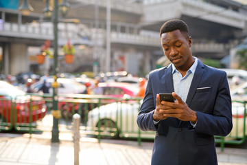 Young handsome African businessman using phone in the city