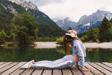 Young sports woman stretching at dock on the lake in the mountains