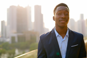 Young handsome African businessman against view of the city